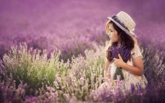 دختر بچه میان دشت گل بنفش زیبا