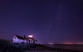 عکس شب پر ستاره با فانوس دریایی روشن زیبا و رویایی