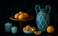 عکس زیبا و حرفه ای از چیدمان ظروف سفالی آبی فیروزه ای و پرتقال ها